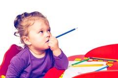 Sueños y mordeduras de la niña un lápiz mientras que se sienta en una tabla, aislada en un fondo blanco Fotos de archivo libres de regalías