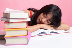 Sue?o asi?tico joven agotado de la mujer con los libros en la tabla fotos de archivo libres de regalías