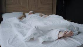 Sue?o de la mujer joven en cama c?moda en una m?scara para dormir Venda en ojo Ma?ana en la habitaci?n Almohada blanca y metrajes