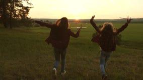 Sue?os del vuelo Concepto feliz de la ni?ez Dos muchachas juegan con un avi?n del juguete en la puesta del sol Ni?os en el fondo  metrajes