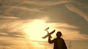 Sue?os del vuelo Ni?os en el fondo del sol con un aeroplano a disposici?n Silueta de los niños que juegan en el avión metrajes