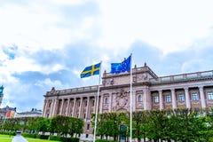 Sueco e bandeiras da UE na frente do parlamento sueco imagem de stock