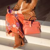 Suede boots on women`s legs. Sunglasses in the hands. Elegant bag with bow. Close-up.  Stock Photography