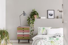 Suede covered pink and olive green nightstand with grey lamp in stylish bedroom with floral sheets and green plants in pots royalty free stock photos