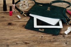 Suede female bag with tablet, notepads, white watch and cosmetic Royalty Free Stock Image