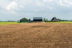 Suelo cultivado delante de un cortijo holandés moderno con los graneros Imagen de archivo libre de regalías