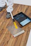 Suelo de madera del rodillo de pintura que impermeabiliza Foto de archivo