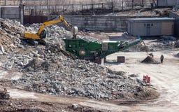 Suelo del cargamento del excavador en la trituradora móvil de la roca Fotografía de archivo