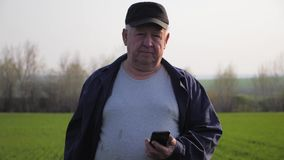 Suelo del granjero maduro y smartphone de examen con que comprueba el informe de la agricultura en un campo metrajes