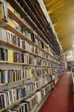 Suelo a los estantes del techo cargados con los libros foto de archivo
