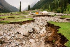 Suelo quebrado por terremoto y la vivienda sola de un granjero de Asia Central foto de archivo