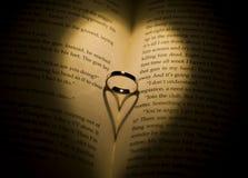 Suene echando una sombra en forma de corazón en un libro Imagen de archivo