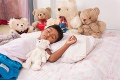 Sueño asiático del muchacho con el oso de peluche Imágenes de archivo libres de regalías