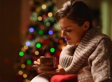 Sueño de la silla que se sienta de la mujer con el chocolate caliente Foto de archivo libre de regalías