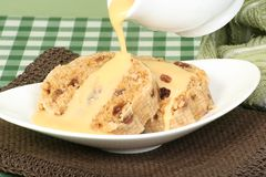Suet pudding and custard. Home made suet pudding with custard pouring on top Stock Photography