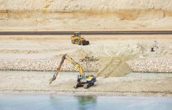 Free Suez Canal Construction Site. Backhoe And Frontend Loader Working In The Sandy Bank. View From The Water, Suez Canal, Egypt Stock Photography - 214496852