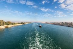 Suez Canal in Egypt. Tugboat accompanies the ships. Royalty Free Stock Image