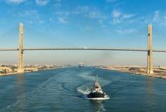 Suez kanal, Egypten, 2017: Bortgång för eskortfartyg för skepp` s till och med den Suez kanalen, i bakgrunden - bron för Suez kan royaltyfri foto
