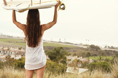 Sufer girl with board. Surf girl looking out at the ocean Stock Photo