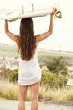 Sufer girl with board. Surf girl looking out at the ocean Stock Image