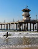 Sufer and Pier. Surfer carries his surfboard at Huntington Beach Pier Stock Image