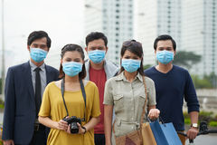 Suffering from air pollution. Asian people looking at camera with dissatisfied face expressions while suffering from air pollution in city center Royalty Free Stock Photography