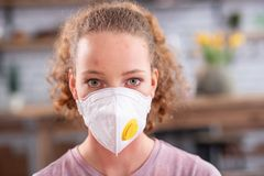 Appealing long-haired girl with light eyes wearing white mask stock images