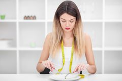 Suffering from anorexia. Image of girl trying to put a pea on th Royalty Free Stock Image