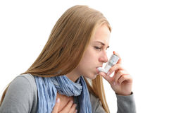 Suffering from asthma. Young woman using an asthma inhaler as prevention Royalty Free Stock Photo