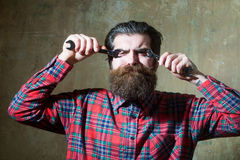 Suffering bearded man fastening eyes with wrenches royalty free stock image
