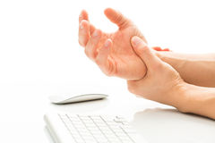 Suffering from a Carpal tunnel syndrome. Working too much - suffering from a Carpal tunnel syndrome - young man holding his wrist in pain due to prolonged use of Royalty Free Stock Image