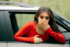 Car Sick Woman Having Motion Sickness Symptoms. Suffering girl in a pulled over automobile trying to recover from travel sickness Royalty Free Stock Images