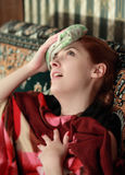 Suffering girl stupes a towel to her head royalty free stock image