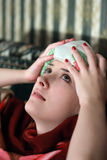 Suffering girl stupes a towel to her head Royalty Free Stock Images