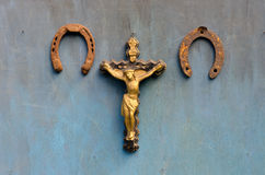 Suffering of Jesus Christ and two  rusty horseshoe on blue wooden wall Royalty Free Stock Image