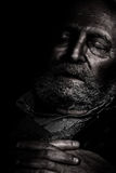 Suffering and loneliness elderly. An elderly man with closed eyes is living his last moments of life. Hands crossed. Isolation and neglect of older concept stock image