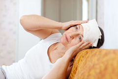 Woman stupes  towel to her head Stock Image
