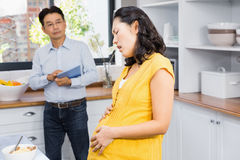 Suffering pregnant woman touching her belly Stock Photos