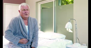 Suffering senior man holding his belly. On bed stock video footage