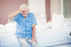 Suffering senior man holding his head st home Royalty Free Stock Photography
