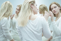 Suffering from a serious mental disorder. Young woman in white trying to touch an illusionary image of her own Stock Images