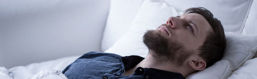Suffering from sleeplessness. Man suffering from sleeplessness lying with open eyes Royalty Free Stock Photo