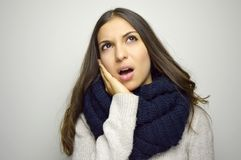 Suffering from toothache. Beautiful young woman with scarf touching her cheek standing against gray background Stock Image