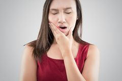 Suffering from a toothache. Beautiful young woman suffering from a toothache while standing against grey background royalty free stock images