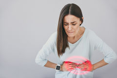 Suffering young woman filling pain in her stomach. stock photos