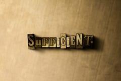 SUFFICIENTE - il primo piano dell'annata grungy ha composto la parola sul contesto del metallo fotografie stock