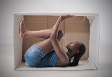 Suffocating space. Young african woman stuck in a carton stock photo
