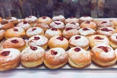 光明节庆祝的多福饼sufganiyot在面包店商店 免版税库存照片