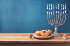 Sufganiyot e menorah do feriado do Hanukkah na tabela de madeira foto de stock royalty free
