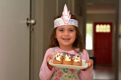 Sufganiyot - Hanukkah Jewish Holiday Food. Jewish child (girl age 05) carries a plate full with mini Sufganiyot / doughnuts filled with strawberry jelly on Stock Images